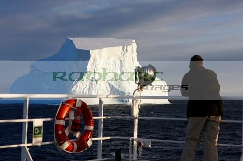 man taking photograph of giant iceberg on board ship in antarctica