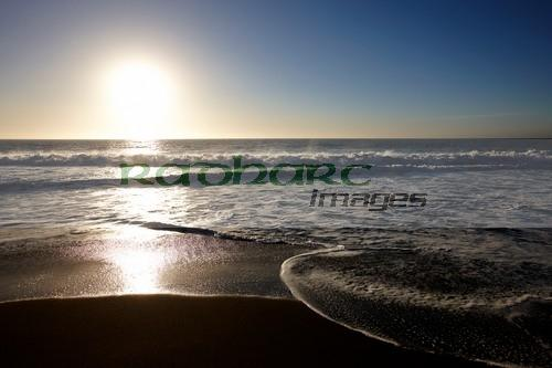 sun setting over sandy beach on the pacific ocean los pellines chile