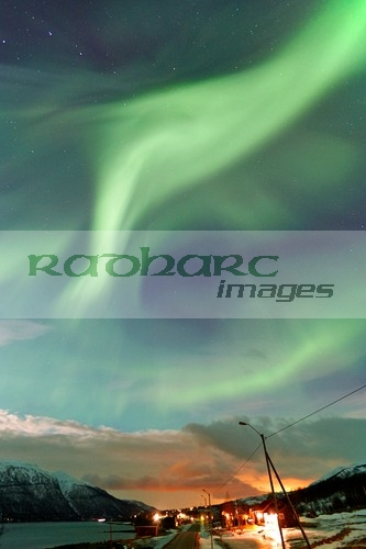 strong swirling northern lights aurora borealis over village near tromso in northern norway europe