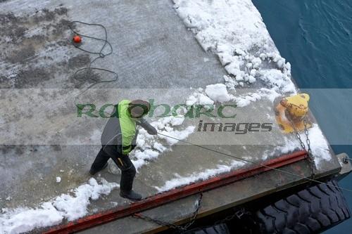 dock worker pulling in ships rope on frozen pier