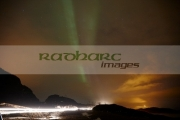 green-purple-streaks-northern-lights-on-cloudy-night-as-cars-go-by-near-tromso-in-northern-norway-europe