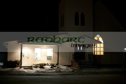 church with porch light on during cold winter night