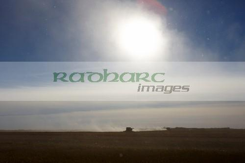 debris thrown up by john deere combine harvesters harvesting on the prairies of Saskatchewan Canada