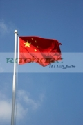 chinese-flag-flying-against-blue-sky-on-flagpole