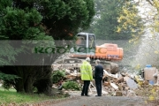man-in-hard-hat-yellow-luminescent-jacket-talks-to-man-in-suit-in-driveway-in-front-fiat-hitachi-JCB-on-construction-site-removing-demolished-old-building-west-belfast-northern-ireland