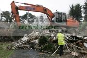 man-in-yellow-flourescent-day-glo-jacket-hard-hat-orange-fiat-hitachi-JCB-on-construction-site-removing-demolished-old-building-west-belfast-northern-ireland