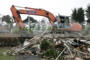 driver-with-cab-door-open-orange-fiat-hitachi-JCB-on-construction-site-removing-demolished-old-building-west-belfast-northern-ireland