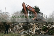 man-waters-rubble-with-water-hose-to-damp-down-dust-in-front-empty-orange-fiat-hitachi-JCB-with-cab-door-open-on-construction-site-removing-demolished-old-building-west-belfast-northern-ireland