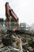 empty-orange-fiat-hitachi-JCB-with-cab-door-open-on-construction-site-removing-demolished-old-building-west-belfast-northern-ireland