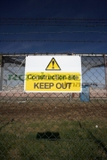 construction-site-keep-out-sign-on-chain-link-fence-surrounding-redevelopment-building-site-with-old-factory-in-the-background