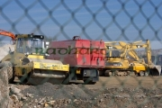 plant-equipment-behind-chain-link-security-fence-on-construction-building-site-in-northern-ireland-uk