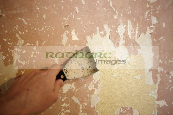 mans hand stripping paint off walls in a house