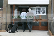 man-woman-entering-polling-station-in-northern-ireland-with-dogs-tied-up-outside