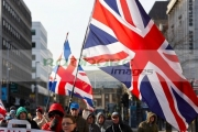 hooded-protester-carries-union-flag-through-Belfast-during-ongoing-protests-against-Belfast-City-Councils-decision-to-only-fly-the-Union-Flag-on-designated-days.-Belfast-City-Centre,-2nd-February-2013
