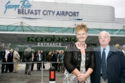 Barbara-McNarry-Dickie-Best-in-front-Belfast-City-Airports-new-logo-at-George-Best-airport-renaming-ceremony,-Belfast-City-Airport,-Belfast,-Northern-Ireland.