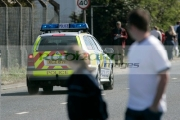 Pedestrians-watch-PSNI-Police-Service-Northern-Ireland-vehicle-on-call-speed-past,-Newtownards,-Northern-Ireland