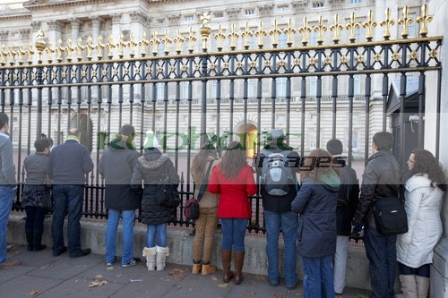 Tourists staring through the gates of Buckingham Palace