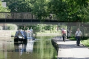 narrowboat-on-nottingham-canal-beside-towpath-with-pedestrians-footbridge-nottingham-england-