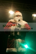 Man-dressed-as-santa-performs-on-stage-in-front-lights-with-radio-microphone-mic-Belfast-Northern-Ireland