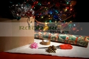 box-to-be-wrapped-up-with-scissors-wrapping-paper,-decorations-tape-in-front-christmas-tree