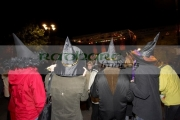 four-women-dressed-as-witches-wearing-hats-watch-stage-entertainment-guildhall-square-rear-view-Halloween-Derry-Ireland