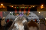 woman-with-brown-hair-wearing-bat-wing-head-dress-watches-stage-entertainment-guildhall-square-Halloween-Derry-Ireland