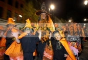 schoolchildren-teachers-dressed-as-orange-pumpkins-parade-down-shipquay-street-Halloween-Derry-Ireland