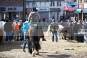 man-in-cowboy-hat-riding-horse-down-main-street-during-ballyclare-may-fair-county-antrim-northern-ireland
