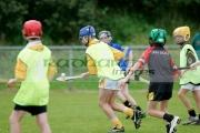 teenage-boy-wearing-protective-helmet-yellow-bib-balances-hurley-ball-sliothar-on-hurling-stick-caman-during-practise-game