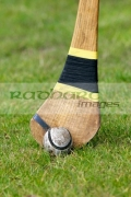 used-leather-sliothar-hurling-ball-beside-head-caman-hurley-stick-on-grass