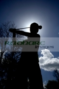 silhouette-young-golfer-holding-golf-club-driver-about-to-swing-to-strike-the-ball-against-blue-cloudy-sky