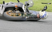 rider-in-leathers-helmet-lying-underneath-bike-during-motorbike-crash-trackday