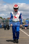 motorsport-male-driver-in-fire-proof-overall-suit-helmet-walking-along-pit-lane