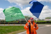 motorsport-marshall-in-orange-jacket-waves-green-blue-flags