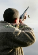 man-with-glasses-in-fleece-jacket-firing-shotgun-into-sky-with-cartridge-ejecting-on-december-shooting-day,-county-antrim,-Northern-Ireland