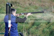 man-in-blue-overalls-with-tatoo-firing-shotgun-into-field-from-shooting-stand-on-december-shooting-day,-county-antrim,-Northern-Ireland