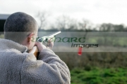 man-with-glasses-in-fleece-jacket-firing-shotgun-into-field-with-cartridge-ejecting-on-december-shooting-day,-county-antrim,-Northern-Ireland