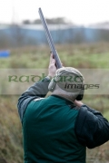 Man-in-hunting-clothes-ear-defenders-takes-aim-with-shotgun-in-shooting-stand-on-december-shooting-day,-county-antrim,-Northern-Ireland