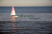 small-pink-white-topaz-dinghy-sail-boat-sailing-across-the-water-in-evening-sunlight-reflecting-in-the-water