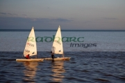 two-laser-class-sailing-boats-from-gbr-IRL-great-britain-ireland-sailing-in-evening-sun-with-reflection-on-the-water