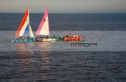 small-pink-white-red-white-blue-topaz-dinghy-sail-boats-sailing-being-towed-by-inflatable-across-the-water-in-evening-sunlight