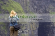 blonde-haired-female-tourist-taking-photos-at-the-Cliffs-Moher,-County-Clare,-Republic-Ireland