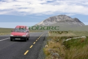 red-van-on-road-at-Errigal-mountain-donegals-highest-peak-against-blue-sky-between-dunlewey-letterkenny-white-quartzite-conical-cone-county-Donegal-Republic-Ireland
