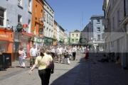 people-walking-down-pedestrian-william-street-past-street-entertainer-Galway-city-county-Galway-Republic-Ireland