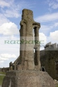 12th-century-cross-St-Patrick-against-blue-cloudy-sky-in-the-Rock-Cashel,-Cashel,-County-Tipperary,-Republic-Ireland