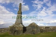 remains-high-stone-celtic-cross-on-OScally-monument-with-mausoleum-against-blue-cloudy-sky-in-the-Rock-Cashel,-Cashel,-County-Tipperary,-Republic-Ireland