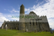 12th-century-round-tower-13th-century-cathedral-against-blue-cloudy-sky-in-the-Rock-Cashel,-Cashel,-County-Tipperary,-Republic-Ireland
