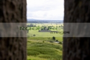 viewpoint-looking-out-through-stone-fortifications-towards-hore-abbey-from-the-Rock-Cashel,-golden-vale-Cashel,-County-Tipperary,-Republic-Ireland