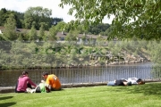 tourists-lie-on-the-grass-soaking-up-the-sunshine-in-avoca-village-county-wicklow-overlooking-the-river