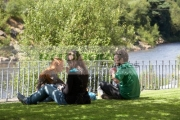 three-foreign-tourists-make-an-impromptu-lunch-picnic-sitting-on-grass-lawn-in-front-fence-overlooking-river-in-vale-avoca
